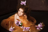 Girl with lilac lilies in her hair — Stock fotografie