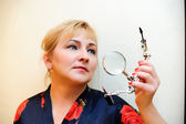 Housewife with a magniglass — Stock Photo