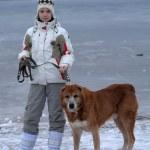 Teen girl walking a large dog in winter — Stock Photo