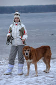 Teen girl walking a large dog in winter — Stockfoto