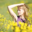 Girl relaxing in field of flowers — Stock Photo