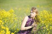 Girl relaxing in field of flowers — Stock Photo