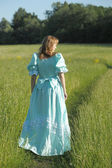 Young woman in an retro dress in the field — Stock Photo
