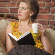 Stock Photo: Womwith book and cup in chair.