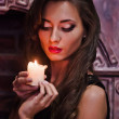 Portrait of a beautiful woman with a candle — Stock Photo #9233247