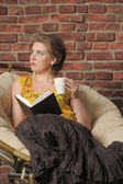 Woman with a book and a cup in the chair. — Stock Photo