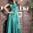 Young beautiful woman in an emerald dress — Stock Photo