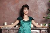 Young beautiful woman in an emerald dress — Stock Photo