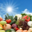 Foto Stock: Fruit and vegetables against sunny sky