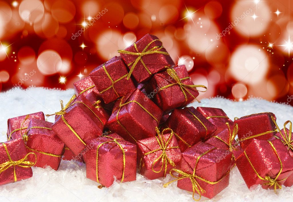 A stack of Christmas gifts in snow on a bokeh lights and stars background — Stok fotoğraf #9310737