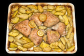 Roasted chicken thighs with potatoes and lemon. — Stock Photo