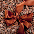 Stock Photo: Brown tape with gold shade fastened by bow lies on many of cocobeans