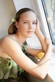 Beautiful girl with lemon near the window — Stock Photo