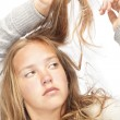 Young blond girl looks at her hair - Stock Photo