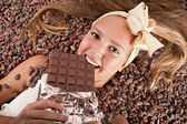 Beautiful girl with chocolate on cocoa beans — Stock Photo