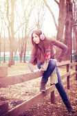 молодая женщина сидит на заборе — Стоковое фото