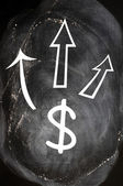 US Dollar symbol with up arrows on blackboard — Stock Photo