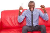 Mannen i soffan med fjärrkontrollen glädjas — Stockfoto