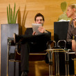 Business man and business woman waiting in office lobby — Stock Photo