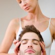 Woman massaging man's temples — Stock Photo