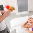 Woman lying on the bed man serving breakfast — Stock Photo