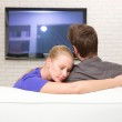 Man watching tv woman embraces him — Stock Photo
