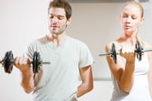 Man and woman lifting dumbbell in gym — Photo