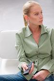 женщина холдинг пульт дистанционного управления — Стоковое фото