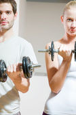 Man and woman lifting dumbbell in gym — Stock Photo