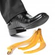 Businessman foot about to slip and fall on a banana peel — Stock Photo #8759958