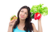 Woman comparing burger and fresh peppers salad — Stock Photo