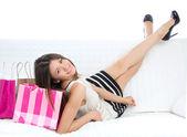 Donna sdraiata su un letto con borse della spesa — Foto Stock