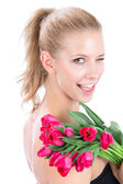 Beautiful woman with bouquet of red tulips flowers winks — Stock Photo