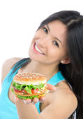 Woman with unhealthy burger in hand — Stock Photo