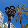 Stock Photo: Street light and palms with luxury apartments building in backgr