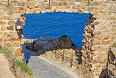 Pass in fortress made of stone as natural frame. Tossa de Mar, S — Stock Photo