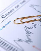 Golden paperclip laying on financial chart. — Stock Photo