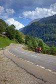 Cyclists on road among swiss alps, Europe. — Stock Photo