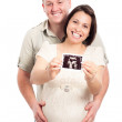 Happy pregnant couple showing ultrasound picture — Stock Photo #10097397