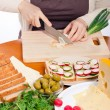 Chopping spring onion and preparing sandwiches — Stock Photo