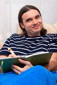 Happy man writing diary on sofa — Stock Photo
