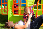 Happy family and colorful playhouse — Stock Photo