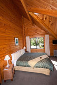 Interior of mountain wooden lodge double bedroom — Stock Photo
