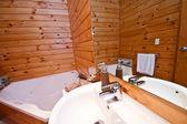 Wooden bathroom interior in mountain lodge — Stock Photo