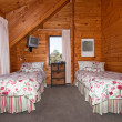 Two beds in wooden lodge bedroom — Stock Photo #9235347