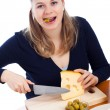 Woman eating olives and cutting emmenthal cheese — Stock Photo #9658283