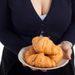 Woman holding plate with fresh croissants — Stock Photo #9658476