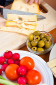 Preparing olives and emmenthal cheese — Stock Photo