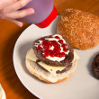 Pouring ketchup on homemade hamburger — Stock Photo #9938092