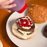 Pouring ketchup on homemade hamburger — Stock Photo